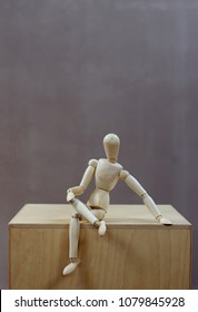 wooden dummy sitting on a wooden box with legs crossed. Grey background. Vertical. Room for text.