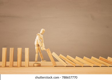 A wooden dummy stopping the domino effect. retro style image executive and risk control concept