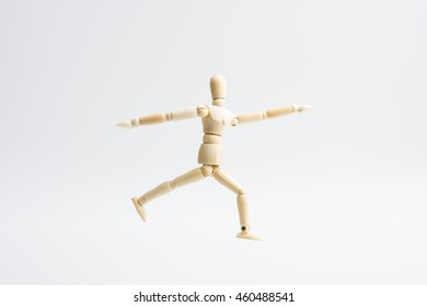 wooden dummy in yoga action isolated on white background