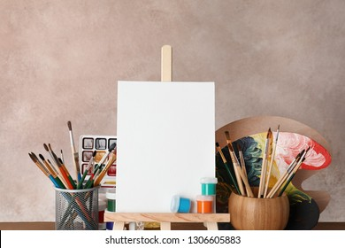 Wooden easel with blank canvas board and painting tools for children on color background
