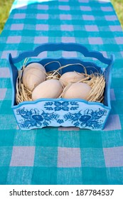 wooden easter eggs in a blue basket