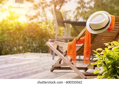 Wooden easy chair on a garden lawn, hat with flower. lounge chair on wooden terrace garden. Paris