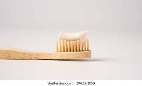 Wooden eco toothbrush with toothpaste on a white background. Bamboo toothbrush.
