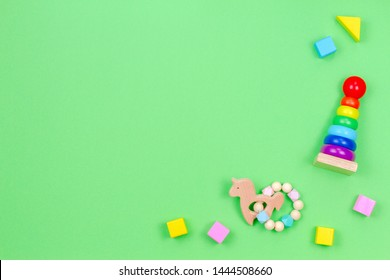 Wooden educational baby toys on light green background. Top view