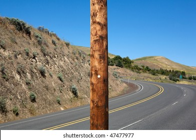 Wooden electric pole outdoor against winding highway