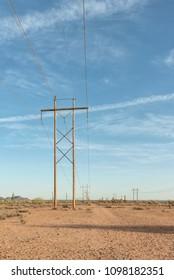 wooden electrical pylons in desert. vertical image.
