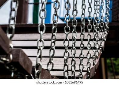 Wooden empty bridge with chains in the children's playground