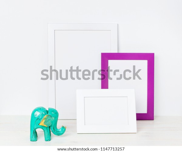 Wooden empty frames for a photo and a wooden emerald elephant on a background of a white wall. Blank paper frames, modern home decor mock-up. Interior accessories, home decor elements.