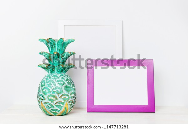 Wooden empty frames for a photo and a wooden emerald pineapple on a background of a white wall. Blank paper frames, modern home decor mock-up. Interior accessories, home decor elements.