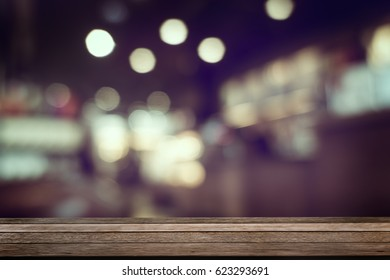 Wooden empty table top with defocus of pub or restuarant or cafeteria with bokeh light background, use for montage or product display, business concept