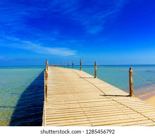 Wooden empty terrace dock or pier. Wooden dock pier blue sea & sky background. View of wooden dock in blue sea. Perspective of old wood pier seashore with clear blue sky & turquoise sea or ocean water