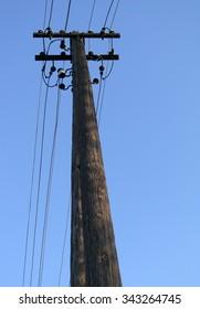 Wooden energy pole against the blue sky.