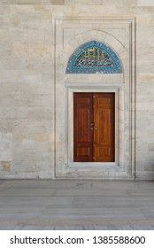 Wooden engraved door on stone wall and tiled marble floor. Arabic text above door says: In the name of Allah, The entirely merciful, the especially merciful