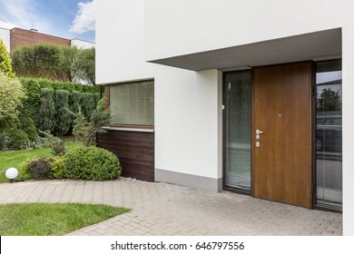 Wooden entrance door to modern white house with paving footpath and backside garden