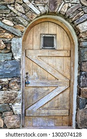 Wooden exterior weathered wine celler door with small window. Stock Image.