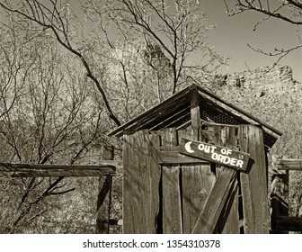 Wooden Falling Down Outhouse in the Old West with Out of Order Sign in black and white