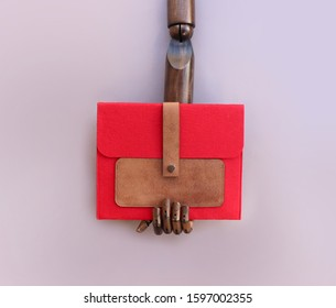 A wooden fashion dummy hand holding a red felt and leather clutch, on lilac background