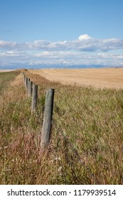 Wooden fence along farm fields leading to distant mountains