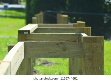 A wooden fence is being built. It consists of horizontal and vertical posts, many still to be put in place. The background is of a green lawn, and a metal fence.