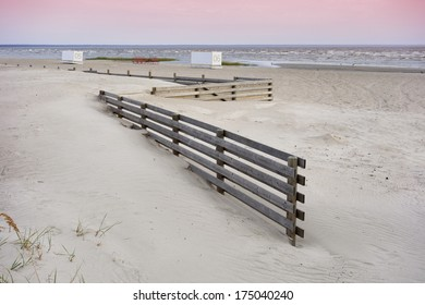 Wooden fence and changing rooms in empty P���¤rnu beach, Estonia. Cubicles. Off season.