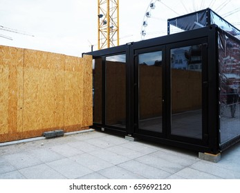 Wooden fence of construction site with modern black office room, glass empty place for street ads, advertisement board, mock up, mockup, signage, urban, industry background.