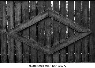 A wooden fence with an dimond shape attatched to the fence black and white