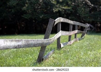 A wooden fence in a field, missing a board and leaning.