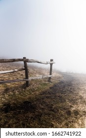 Wooden fence in foggy meadow