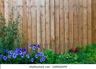 Wooden fence in a frame of green and purple flowers
