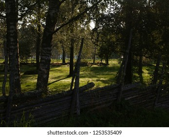 a wooden fence in front of a sunny clearing in Smaland, Sweden