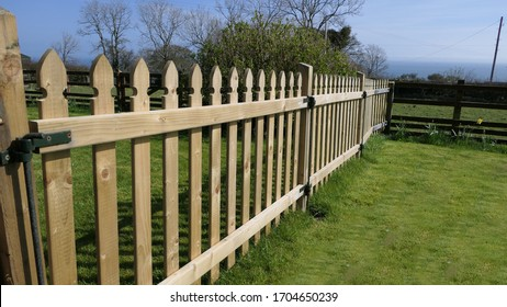 Wooden fence and gate for children on a garden lawn