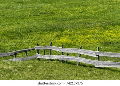 Wooden fence with green grass in the Alps. Country summer landscape.
