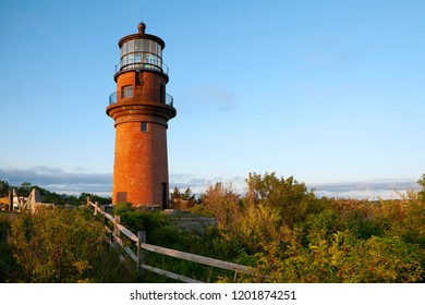 Wooden fence leads to the large brick tower of Aquinnah lighthouse, also referred to as Gay Head light, on a late summer day on Martha's Vineyard island in Massachusetts.