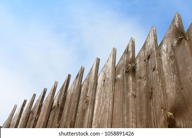 Wooden fence looking like a saw against the blue sky on a diagonal