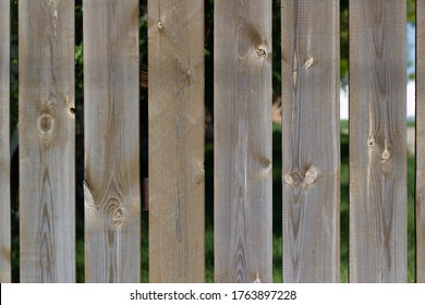A wooden fence made of vertical decorative planks. Wooden fence made of planks.