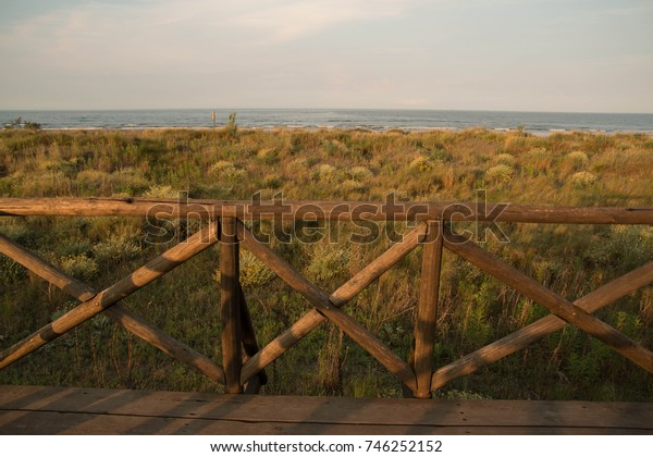 Wooden fence, meadow and sea sunset landscape. Porto Caleri marine botanical park, Italy.