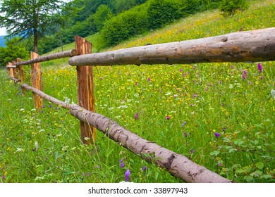Wooden fence near green meadow in mountains