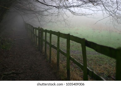 Wooden fence next to a path in winter mist