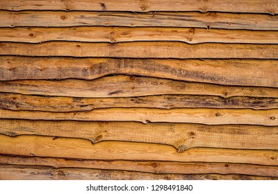 Wooden fence from oiled rough pine planks attached one on one. Horizontal wood texture
