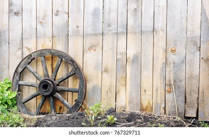 Wooden fence and an old wooden wheel from a dray