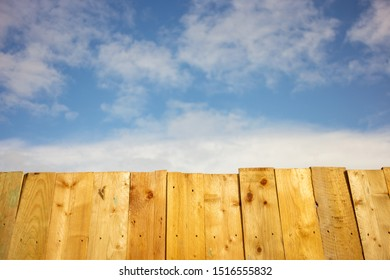 wooden fence on a background of blue sky with clouds
