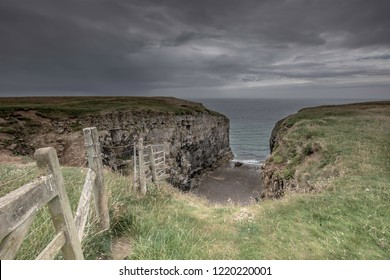 Wooden fence on cliff edge and old limestone quarry on Pembrokeshire coast, South Wales,UK.View from cliff top, coastal path.Dramatic sky with dark rain clouds over british coastline.Landscape UK.