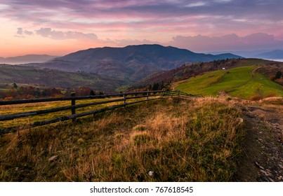 wooden fence on a grassy rural hillside at autumn dawn. gorgeous landscape in forested mountains with red foliage