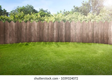 Wooden fence on green garden with sunlight background