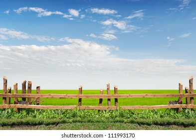 wooden fence on green meadow with a  great blue sky background