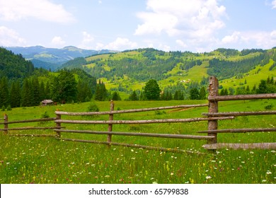 wooden fence on green meadow in mountains