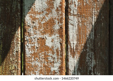 Wooden fence with peeling paint an sunspot texture