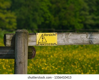 "wooden fence with a sign saying ""careful, electric fence"" in German"