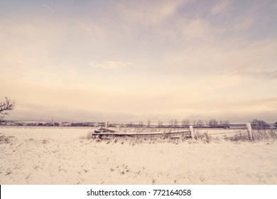 Wooden fence in a winter landscape with snow on a field in the morning
