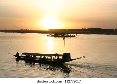 Wooden ferry boats cross the Niger river in Mali during sunset near Timbuktu